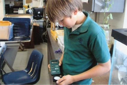 Student at St. Michael Lutheran school in Florida uses a light meter to record lighting levels in the school