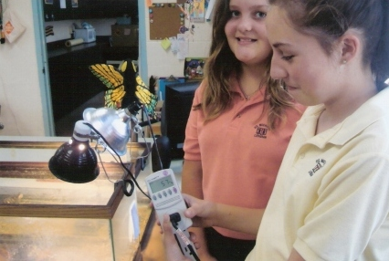 Students at St. Michael Lutheran school use a watt meter to record energy usage