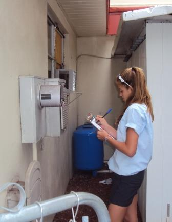 Student at St Michael Lutheran School in Florida reads and records the school's electricity and water meters