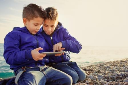 two boys outside on an ipad