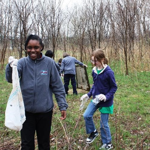 Two Rivers Middle School students clean up waste on campus.