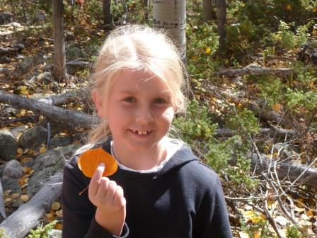 A young girl with a leaf she found while walking in the woods