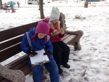 Students sitting on a bench in the snow record their observations of the outdoors
