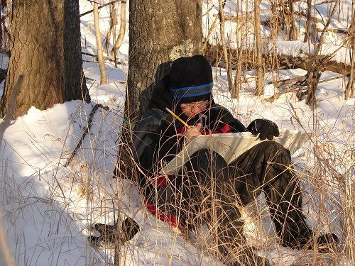 student-sitting-against-tree-in-snow-writing-poetry