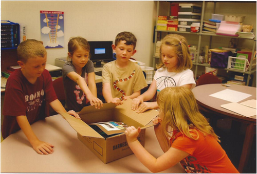 students-around-box-of-supplies-on-table