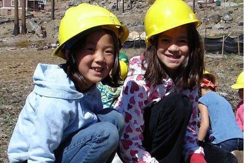 two-girls-smiling-kneeling-on-dirt-planting