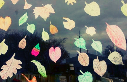 vibrant and colorful paper cut outs of different leaf shapes stuck to a window