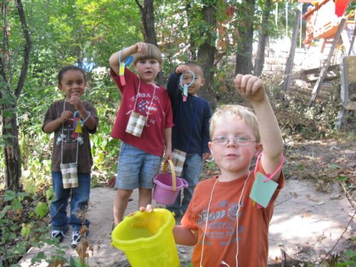 Group of four young children wear their shape bracelets on their wrist.  They are looking for nature object that match their shapes.