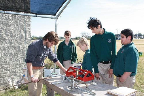 Students and their teacher at a school in Houston work on building a piece of equipment in the outdoors.