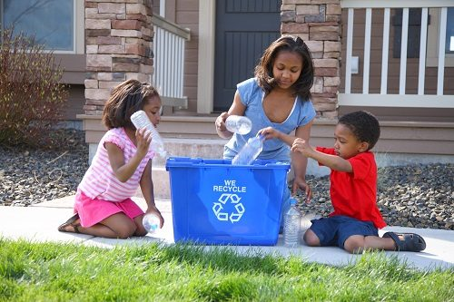 african-american-family-placing-bottles-in-blue-recycling-bin