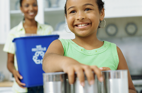 A young African American girl sorts tins to put in a blue recycling bin held by her mother.