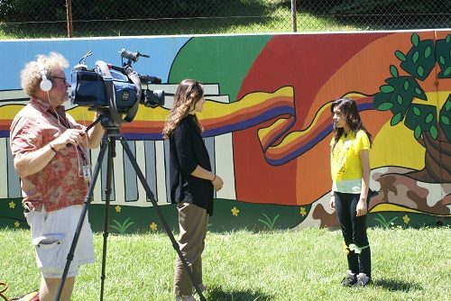 ABC Channel 7 film crew interview a student in front of school mural in Washington, DC.