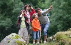 A family look through binoculars while walking in the forest