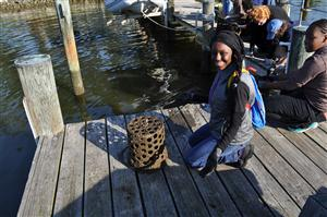 Student sitting on a dock with a barrel of oysters