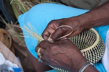 Hands weaving sweetgrass into beautiful baskets