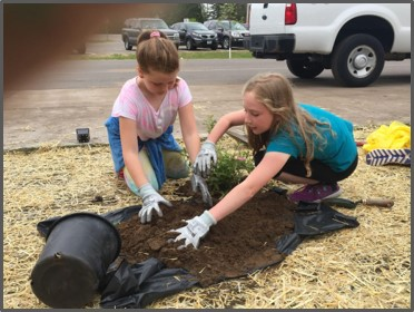 two-girls-gather-soil-for-planting