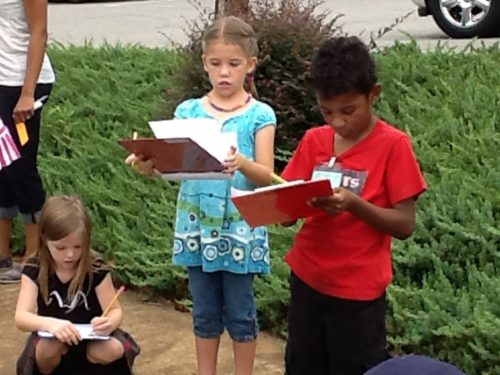 young-boy-girl-writing-clipboards-outdoors