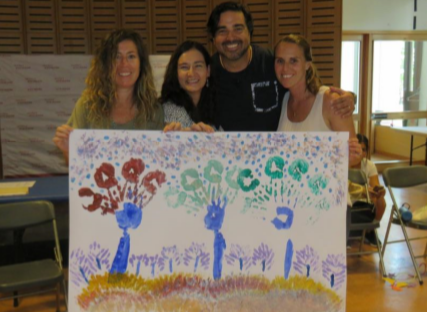 Educators in front of a finger painting of trees