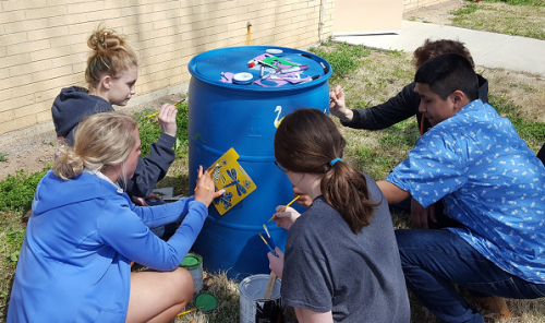 children decorate a rain barrel