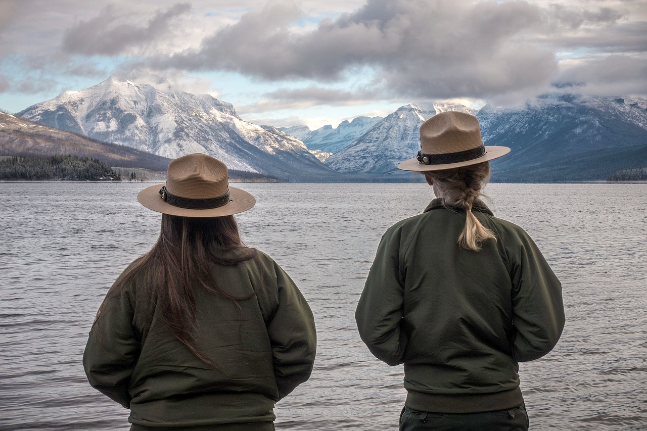 Two female foresters in uniform overlooking a lake with mountains in the background