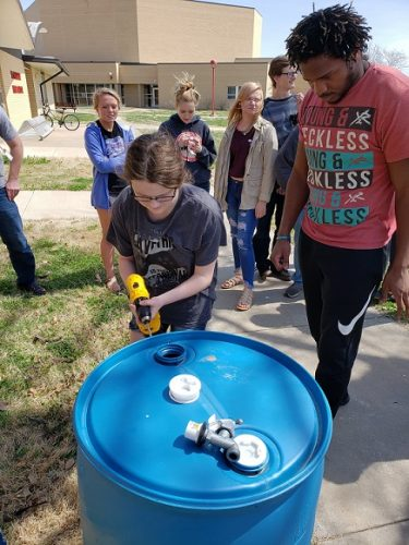 students drill holes into a rain barrel
