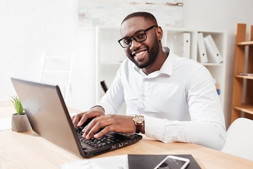 Portrait of smiling african american businessman in white shirt working on his laptop in office