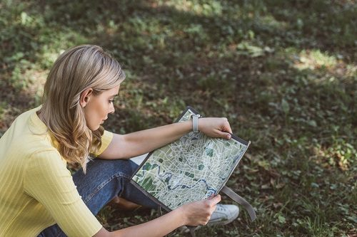 young woman sitting on ground outdoors looking at map