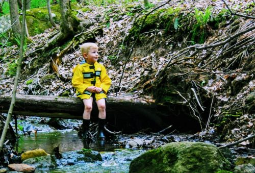 child sitting on a log over a creek