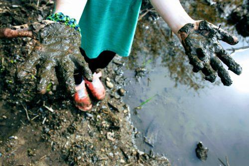 child showing their muddy hands