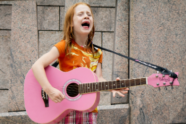 girl singing with a pink guitar