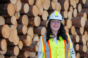 Female logger standing in front of stacked logs