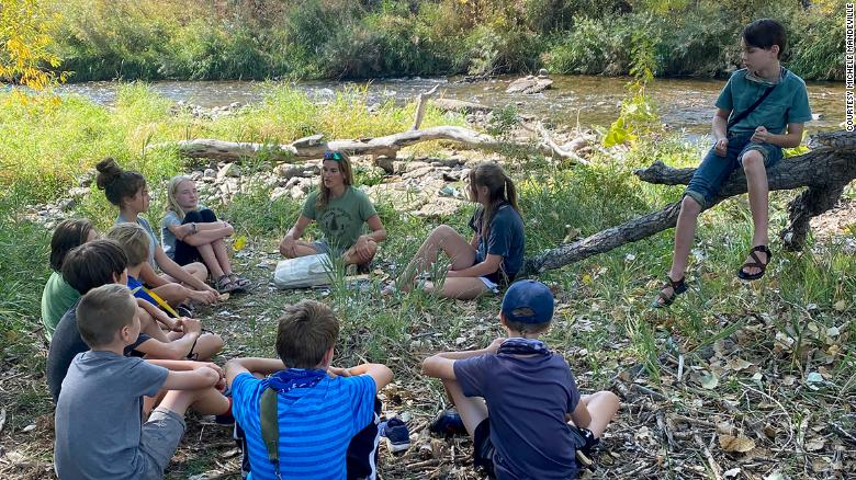 Children sit in a circle during a Project Learning Tree outdoor classroom activity.