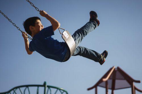 young-boy-swinging-on-swingset