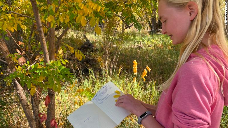 A student writes in her nature journal outdoors.