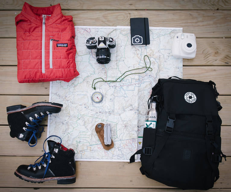 overhead-photo-of-backpack-boots-cameras-map-jacket-and-compass