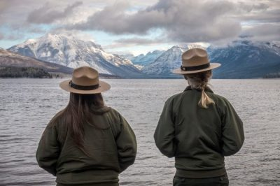 two young women in national park service hats and jackets stand before snow covered mountains