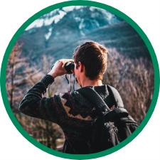 young man looks through a pair of binoculars