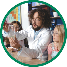 Latino teacher shows two young female students solution in a beaker