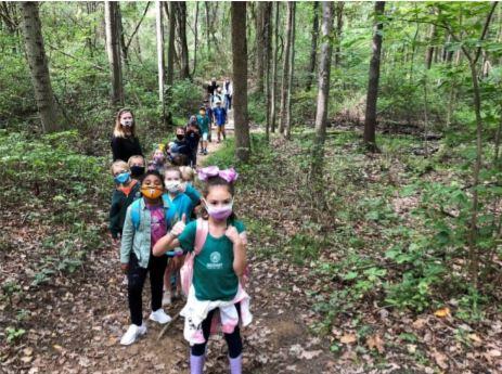 children walk through a forest