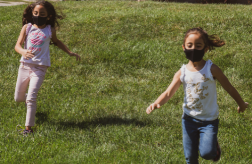 two young girls wearing masks running on grass outside