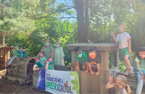 students play on an outdoor wooden train set with a plt greenschool banner hanging